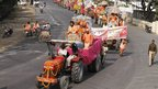 Hindu holy men, sit in tractors as they arrive ahead of the Kumbh Mela, in Allahabad, India, Sunday, Nov. 11, 2012. 