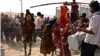 A young Indian child dressed as the Hindu God Shiva leaps into the air as he dances with others during a religious procession at Sangam in Allahabad on November 27, 2012.
