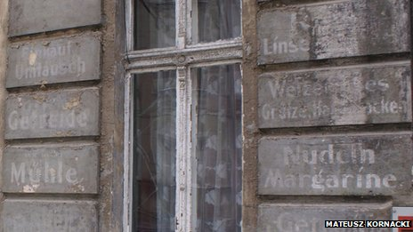 Peeling paint on buildings in Wroclaw, Poland reveals German writing.