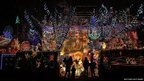 People gather to look at Christmas festive lights that adorn a detached house in a suburban street in Melksham, England