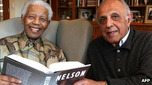 Former South African President Nelson Mandela posing with a copy of the British edition of his book Conversations with Myself with  fellow former political prisoner Ahmed Kathrada