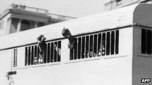 Eight of the Rivonia trial defendants leaving the Palace of Justice in Pretoria on 16 June 1964 with their fists raised in defiance through the barred windows of the prison car