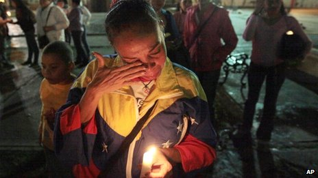 A woman holding a candle for Chavez