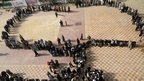 Voters stand in line outside a polling station in Cairo, 15 December