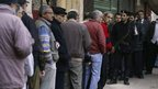 Men queue outside a polling station in Cairo, 15 December