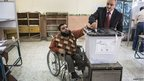 A disabled man receives help to cast his vote in Cairo, 15 December