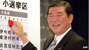 The LDP Secretary-General, Shigeru Ishiba, puts the party's first rosette by a success candidate's name at party headquarters in Tokyo
