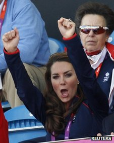 The Duchess of Cambridge cheers while Princess Anne sits impassively in the row behind her at a stadium