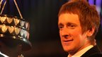 2012 Sports Personality of the Year Bradley Wiggins holds the trophy aloft after being presented it by the Duchess of Cambridge