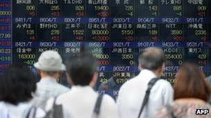 Investors looking at stock board in Japan