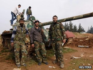 Syrian rebels pose with a tank they captured at the Hananu military academy in Aleppo (16 December 2012)