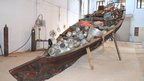 Wooden Kerala style rice boat, filled with household goods by artist Subodh Gupta