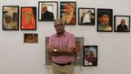 Indian painter Atul Dodiya standing in front of some of his works