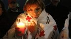 A woman wrapped in a Red Cross blanket