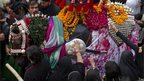 Shia women touch a horse, symbolising the horse that carried Imam Hussein during the battle of Karbala in Rawalpindi, Pakistan.