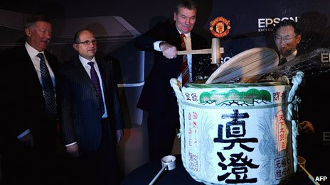Alex Ferguson grins as Man Utd chairman David Gill spills the sake, to mark a deal on a new sponsorship deal with Epson