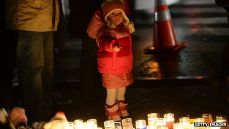 A young child points at candles in Newtown, Connecticut