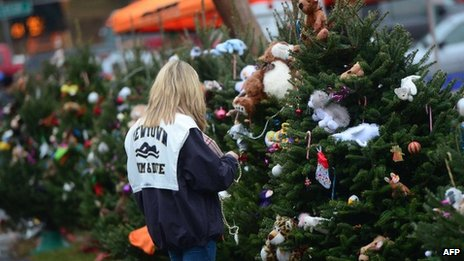 A teenager decorates Christmas trees set up at a makeshift shrine to the victims of a elementary school shooting in Newtown, Connecticut, 16 December 2012