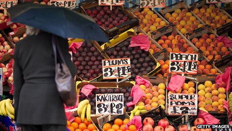 Woman surveys fruit for sale at a market