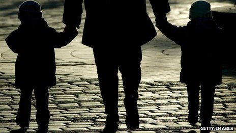 Silhouette of a woman holding hands with two children