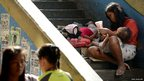A homeless mother with her two children beg for alms on an overpass in Quiapo, Manila,