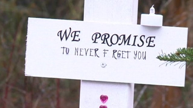 Grave marker saying 'We promise to never forget you'