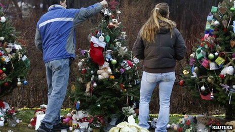 People placing an angel on top of a Christmas tree at a makeshift memorial in Newtown, Connecticut, 18 December