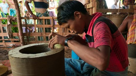 A man makes a stove in the Irrawaddy Delta