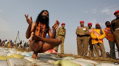A Naga Sadhus, or Hindu holy men, performs yoga postures after taking a holy dip at the confluence of the Rivers Ganges, Yamuna and mythical Saraswati during the 45-day long Ardh Kumbh Mela festival in Allahabad, India, Monday, Jan. 15, 2007.