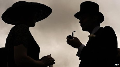 Two racegoers are silhouetted at Royal Ascot