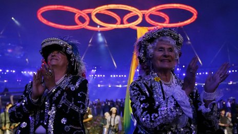 Performers clap as the Olympic rings are seen above, during the opening ceremony of the London 2012 Olympic Games