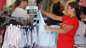 A woman holds a T-shirt inside a shop in Rio de Janeiro, 30 November, 2012