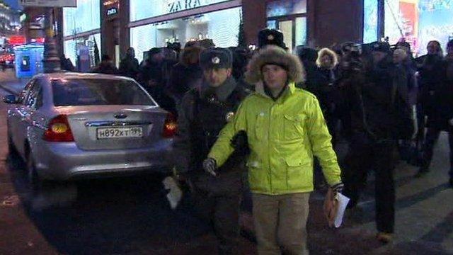 A policeman escorting a protester on to a coach