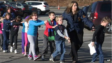 Students exit Sandy Hook Elementary school with help from a police officer