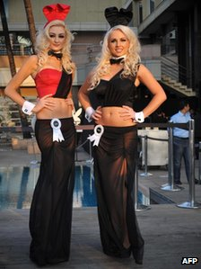 Two playboy bunnies posing in the India adapted costume of long-length skirt, one shoulder top and bare midriffs