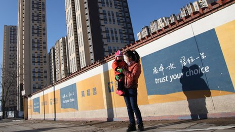 A mother plays with her child on the street that leads to the Jingyuan Road public housing project, the largest one in Beijing
