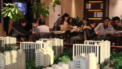 Sales representatives talk to customers behind the East Asia Impression Lake real estate building models