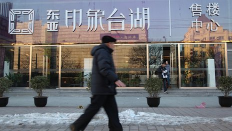A couple comes out of the sales office of East Asia Impression Lake, popular commercial real estate in suburban Beijing