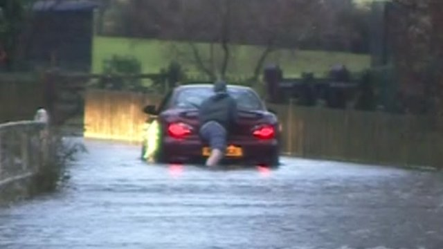 A man pushing his car through flood water