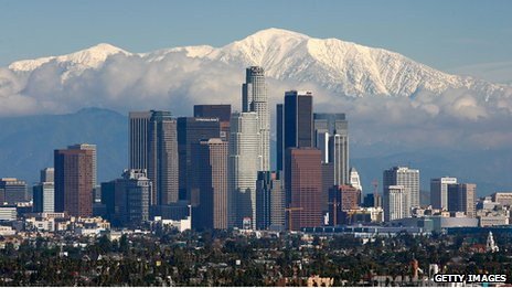 The skyscrapers of Los Angeles climb into a skyline dominated by the snow-covered San Gabriel mountains