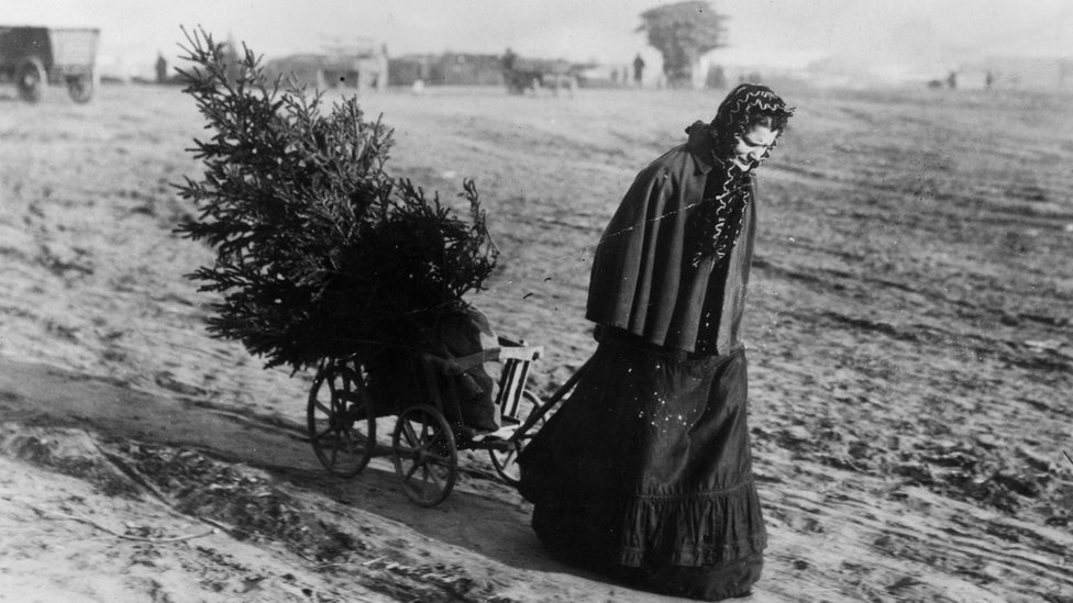 A woman returns home from the market with a Christmas tree, circa 1895
