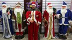 A man arranges Father Christmas costumes as he waits for customers at a wholesale market in Wuhan, China