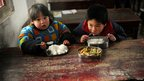 Students have lunch in the classroom of their primary school in Dabie Mountain, Anhui, China