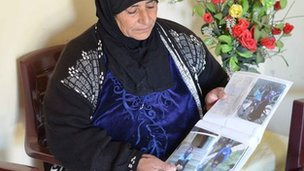 Raya al-Hamoud Aoueishi with photos of her daughter Nadia