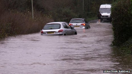 Cars submerged in water on a flooded road in Wallington