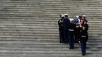 Hawaii Senator Daniel Inouye is carried up the steps of the Capitol to lie in state in Washington, DC 20 December 2012