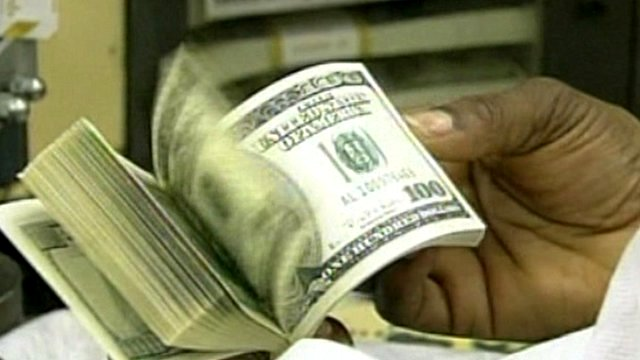 Man flicking through bundle of $100 bills