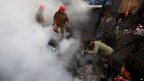 Indian firefighters tackle a fire that broke out at clothes shop at a supermarket in Agartala