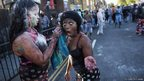 Revellers cover each other in paint and flour on the family day at the Notting Hill Carnival