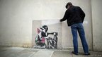 A man inspects a plastic cover placed over an artwork attributed to Banksy
